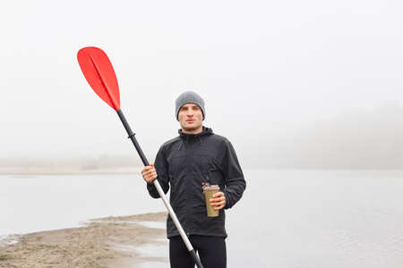 Handsome attractive man on bank of lake or river, holding red oar and thermo mug in hands, looking pensively into distance, guy wearing black jacket and gray cap.