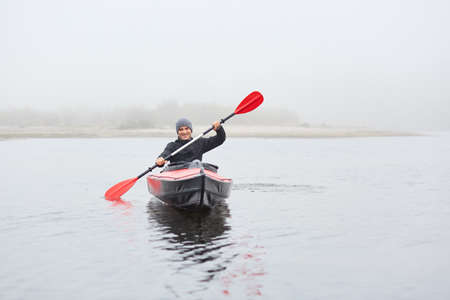 Sports cheerful man in kayak, padding in foggy river in morning, feels happy, laughing sincerely, spending his free time outdoors doing water sport, holding oar in hands, rowing to bank. 免版税图像