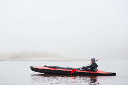 Handsome man paddling canoe on cloudy day, looks concentrated, wearing black jacket and gray cap, holding paddle in hands, spends free time doing water sport and enjoying nature. 免版税图像