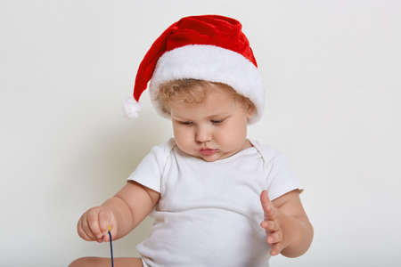 Concentrated baby boy playing with unknown toy, looking down at it, wearing bodysuit and santa hat, keeps palm bit raised, looks attentive, posing isolated over white background. Foto de archivo