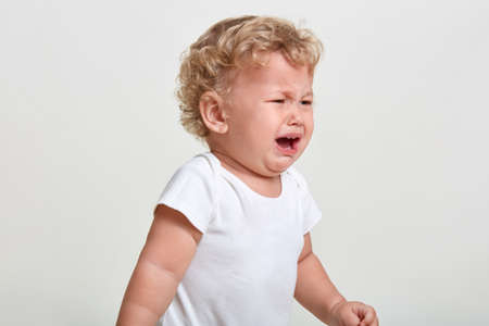 Little boy wearing t shirt cries, being in bad mood, looking away, posing isolated over white background, finding close person, having blond curly hair. Stock fotó