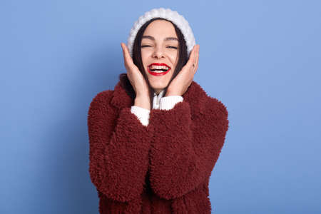 Positive lovely woman with red lips, keeps both hands on cheeks, wears white winter sweater and warm coat, looks at camera with charming smile, isolated over blue wall, lady laughing happily.