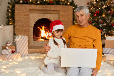 Senior man in yellow shirt sitting on floor and holding laptop on knees, hugging his granddaughter and looks ant camera, cute child looking at notebook screen, dresses santa hat.