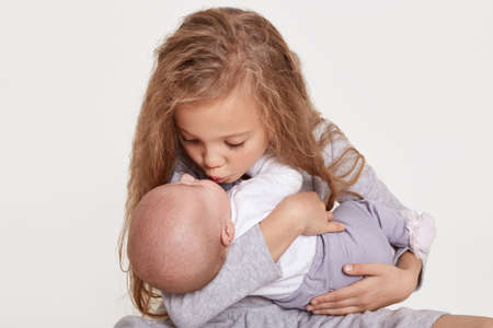 Happy two sisters children posing together isolated over white background, blond female kid kiss her sibling, wearing casual clothing, family love. Childhood.