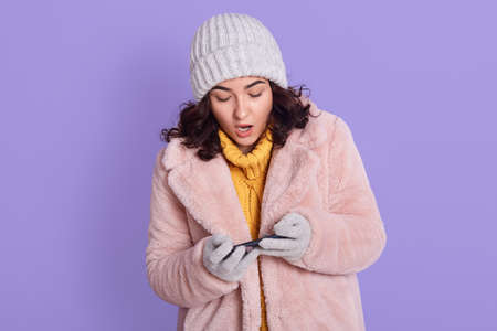 Astonished startled cute dark haired woman in fur coat just won challenge in awesome game, holds smart phone horizonally, plays racing, stares at display amazed, posing isolated over lilac background.