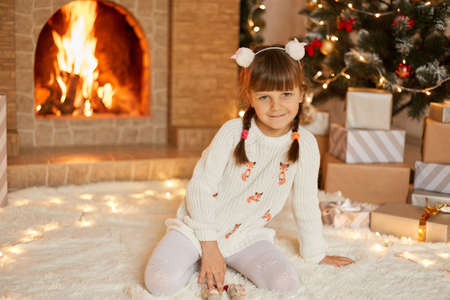 Xmas girl sitting next to festive tree and looking directly at camera, child looking directly at camera, wearing white sweater and tights, happy kid celebrating new year at home near fireplace. Stock Photo