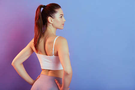 Fitness young pretty woman in gray leggings and white tank top posing backwards with hands on hips, girl with ponytail looking away, standing isolated on color background. Stockfoto