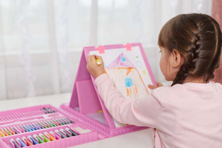 Preschooler little girl with dark hair sitting at table at home and drawing picture, kid painting her house, posing backwards to camera, diligent small artist making illustration. Stockfoto