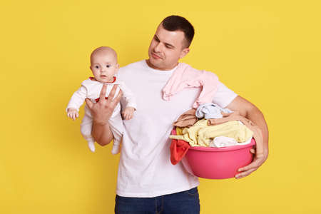 Paternity leave. Young handsome father does laundry, man doing сhild care and housework, male wears white casual t shirt holds his baby and basin with dirty linen in hands, stands against yellow wall.