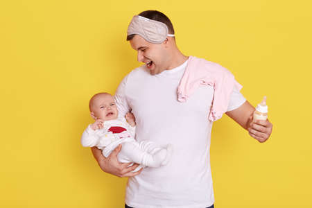 Father with his crying newborn baby posing isolated over yellow background, male tries to calm down infant and feed with milk, handsome guy having fun with her daughter.