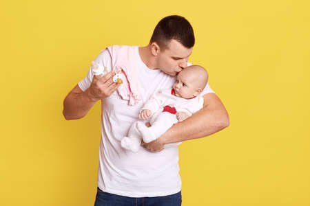 Happy young father looking with tenderness at his baby girl and kissing her on forehead, standing isolated over yellow background, guy wearing white casual t shirt with his tiny child. Stockfoto