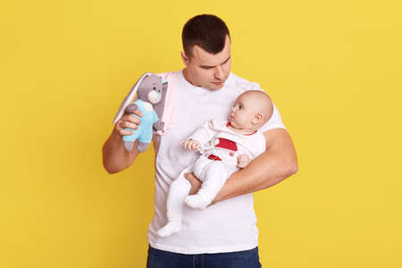 Happy father playing with his baby son or girl with bright rattle, dad holding infant kid and soft toy rabbit in hands, daddy playing with child against yellow wall.