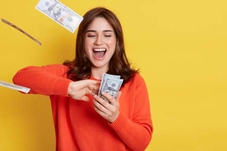 Portrait of very happy young Caucasian woman throwing out money banknotes, yelling something happily, having excited facial expression, keeps mouth opened, stands isolated over yellow background.