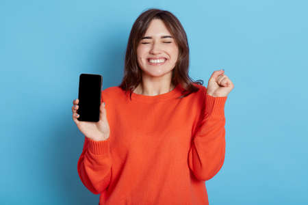 Overjoyed attractive woman keeps fist clenched, being happy to get good news, gets notification on cellphone, wears orange sweater, stands with closed eyes indoor against blue wall, feels amused.