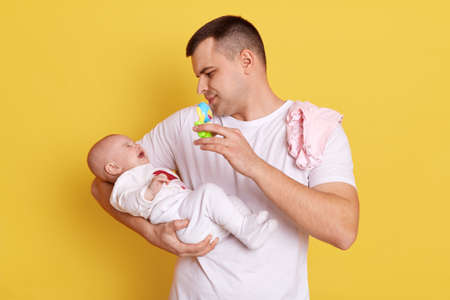 Handsome European man wearing casual white t shirt stands against yellow wall with his newborn baby