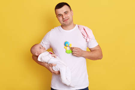 Smiling man wearing casual attire stands against yellow wall with his newborn baby in hands Banque d'images