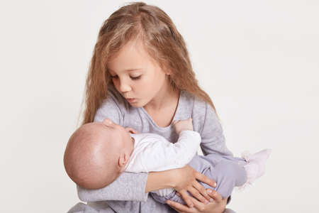 Cute Caucasian girl sister holding little baby indoors. Older sibling with younger sister newborn. Family love bonding together, blond charming female kid looking at baby with love, isolated on white. 版權商用圖片