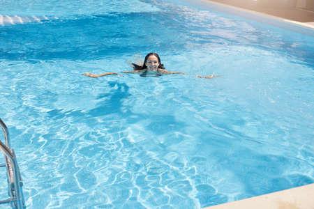 smiling girl enjoying swimming, resting. 免版税图像