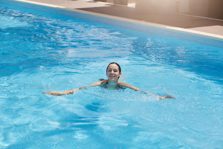 Woman relaxing in pool, smiling happy lady swims in swimming pool.