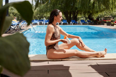 Attractive slim woman sitting near pool in swimsuit. Pretty female sun tanning near water using sunscreen, side view of winsome lady with perfect body.