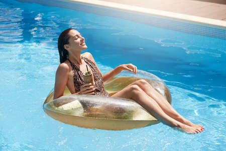 Brunette smiling woman sitting on big rubber ring in middle of swimming pool with cocktail in hand, keeps eyes closed, dressed stylish swimsuit, lady sunbathing on luxury summer resort. 免版税图像