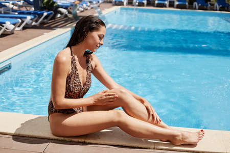 Young slim beautiful woman in bikini applying oil for sun protection, brunette female in swimsuit with leopard print sitting on side of pool and using sunscreen for legs.