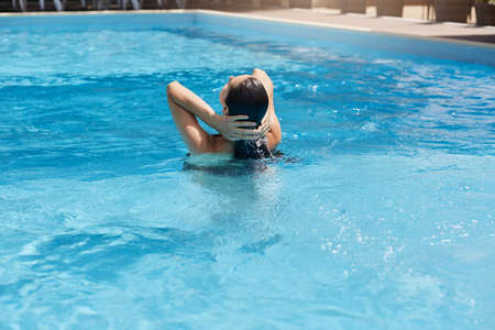 Young woman posing backwards while standing in blue water and touching her wet dark hair, female swims in swimming pool, back view of girl relaxing in drainage basin.