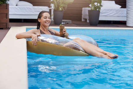 Young European attractive slim tanned woman on swimming ring, holding cocktail in hand and enjoying tropic beverage, wearing stylish swimming suit with leopard print.