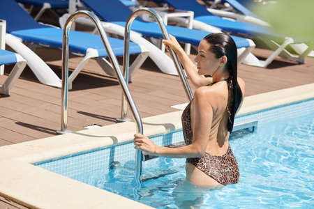 European young lady climbing out of swimming pool, posing backwards, wearing swimsuit with leopard print, looking away, wet girl with perfect body in swimming pool. 免版税图像