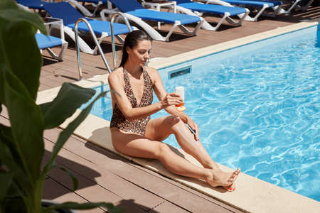European woman in bikini applying protective lotion before sunbathing at pool side, holding sunscreen in hands, wearing swimming suit with leopard print.