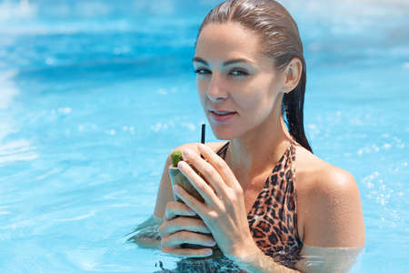 Woman drinking cocktail with straw, looking at camera with flirting and dreaming facial expression, girl with dark wet hair wearing swimsuit with leopard print. 免版税图像
