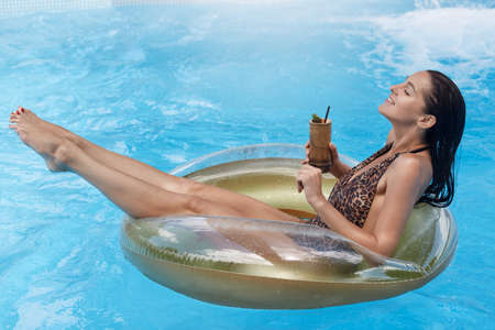 Happy relaxing woman swimming on float in pool, enjoying tropic cocktail, keeps eyes closed, sun tanning in swimming pool, wearing stylish swimsuit, summer vocation.