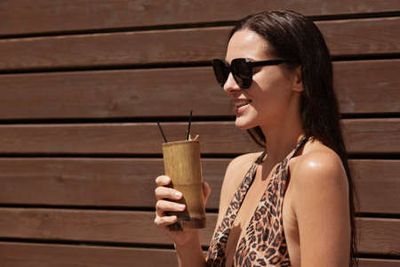 Woman with glass of cocktails posing profile against wooden wall, wearing stylish swimwear with leopard print and sunglasses, enjoying rest at sunny summer day.