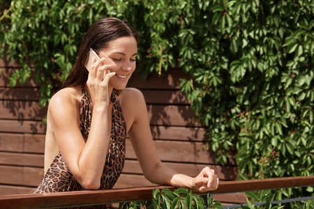 Happy youthful girl communicating via gadget on summer resort, posing near wooden fence with green plants, looking away with expression, has pleasant conversation.