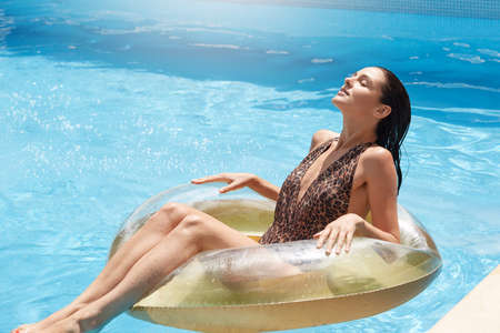 Woman swimming on float in pool, brunette young female with perfect body sun tanning in middle of swimming pool, enjoying sunbathing and sunny day.