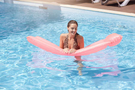 Young pretty woman with rose inflatable mattress floating in pool, looking away and smiling, wet girl in middle of swimming pool enjoying hot sunny day on resort.