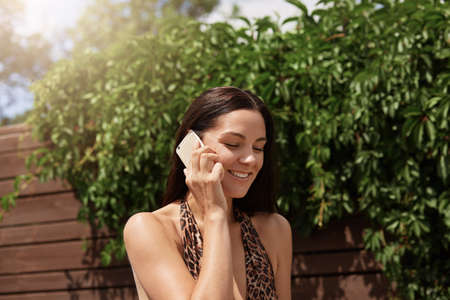 Young woman talking by phone against brown wooden fence, wears swimwear with leopard print.
