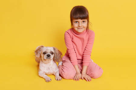 Cute child girl sitting on floor with pet isolated over yellow background, smiling female kid dresses rosy casual attire playing with puppy, charming kid looks at camera.