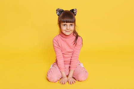 Happy toddler sitting on floor and looking directly at camera, smiling female child wearing casual attire and hair band with cat's ears, isolated over yellow background.