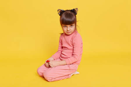 Little dark haired girl looking frowned, sitting on floor against yellow background, toddler wearing casual clothing, offended small kid being upset. 免版税图像
