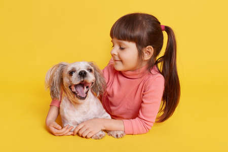 Happy little girl with her dog lying on floor isolated over yellow background, toddler with ponytail looking at puppy with love and hugging her pet, child wearing pink casual clothes.