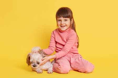 Little girl playing with puppy Pekingese isolated over yellow background, happy laughing dark haired female child looking at camera and hugging her pet, kid expressing positive.