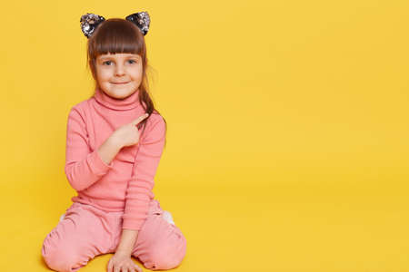 Little European cute girl sitting on floor and pointing aside with index finger, child wearing pink casual clothing and hair band with cat's ears, posing isolated over yellow background, copy space. 免版税图像