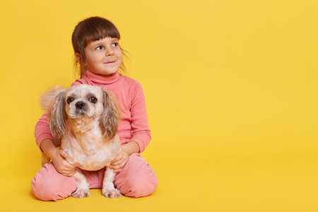 Little girl and puppy posing isolated over yellow background, child hugging Pekingese and looking aside with curious expression, toddler with dark hair wearing casual attire, copy space for promotion. 免版税图像