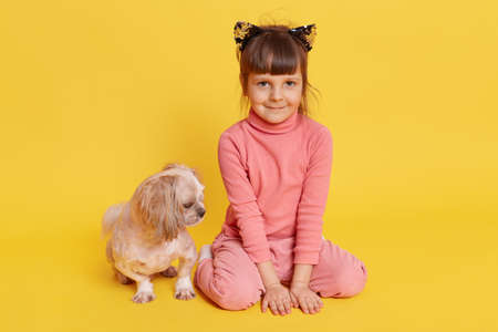 Girl with puppy isolated over yellow background, child looking directly at camera with smile, kid wearing rose sweater, pants and hair band with cat's ears, small kid with Pekingese. 免版税图像