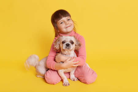 Small kid with funny pony tails glad to be photographed with her favorite Pekingese dog, toddler in pink casual attire, looking directly at camera and embracing her pet. 免版税图像