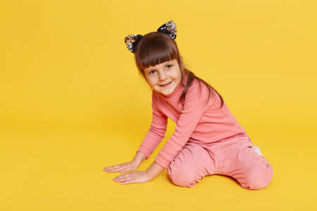 Cute baby girl wearing pink shirt and trousers sitting on floor isolated over yellow background, smiling child in hair band with cat's ears looking directly at camera, touching floor with palms.