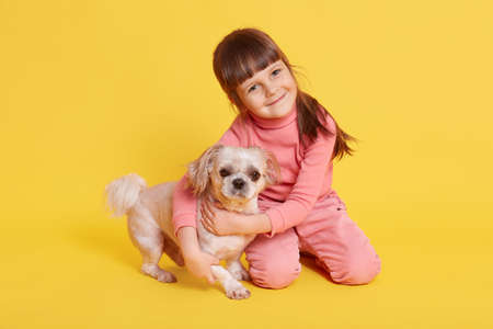 Cute dark haired girl playing with pet dog, looking directly at camera with smile, isolated over yellow background, charming female child with puppy, wearing rose casual attire.