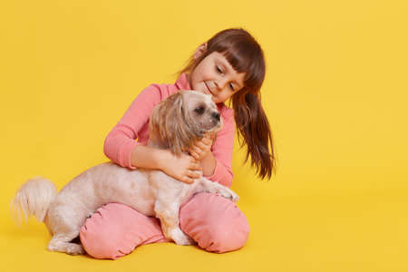 Smiling cute small girl wearing rosy attire sitting on floor against yellow wall, child looking at Pekingese dog and hugging it, toddler kid playing with pet indoor.