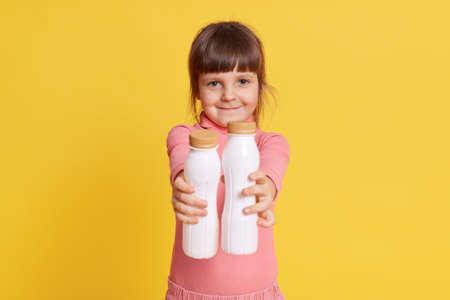 Little dark haired girl dresses pink casual clothing holding plastic bottles of milk, smiling and looking directly at camera with smile, offers organic product, posing isolated over yellow background.